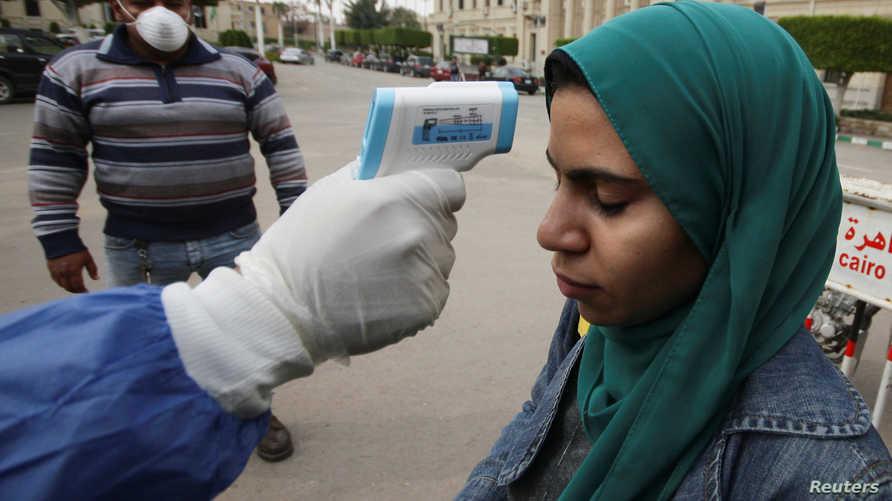 طالبة ماجستير تخضع لفحص درجة حرارتها عند دخولها جامعة القاهرة التي لا تزال بعض البرامج الدراسية مستمرة رغم انتشار وباء كورونا- 15 مارس 2020