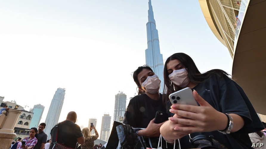 امرأة ترتدي الكمامة وتلتقط سيلفي امام برج خليفة بدبي - 8 مارس 2020