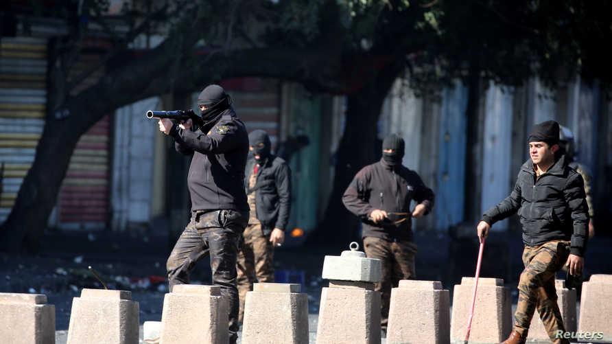 عناصر في قوات الأمن يطلقون الغاز المسيل للدموع على متظاهرين في بغداد