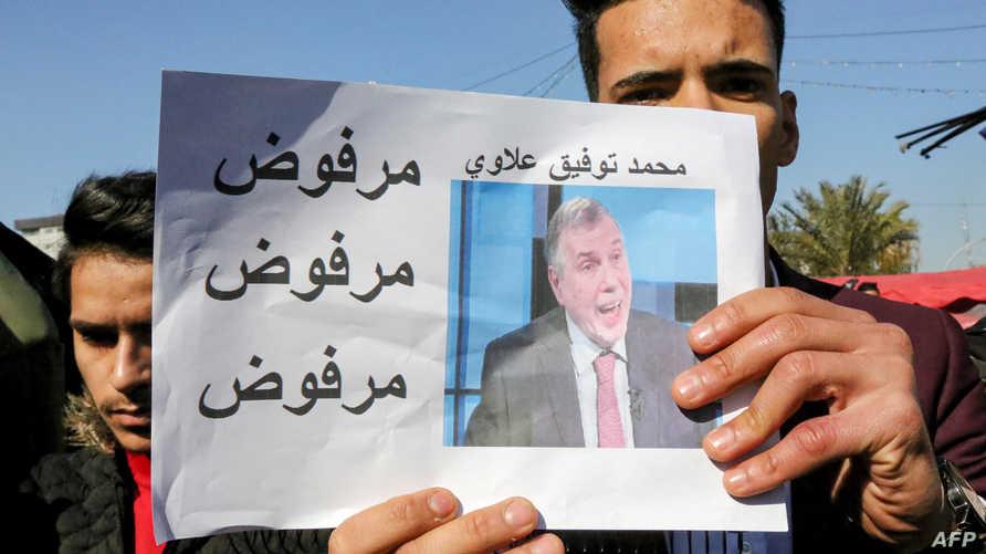 عراقي يتظاهر ويحمل صورة رئيس الوزراء المكلف وقد كتب عليها مرفوض مرفوض مرفوض