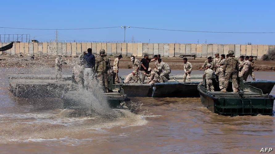 جنود في قوات التحالف يشرفون على تدريبات للجيش العراقي قي معسكر التاجي - أرشيف