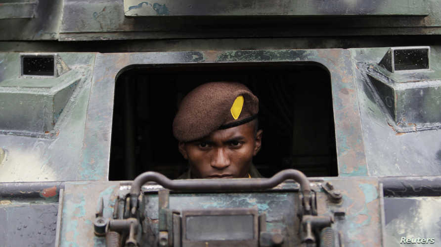 A member of Honduras' military police for public order (PMOP) sits in a tank during a presentation in Mateo, on the outskirts…