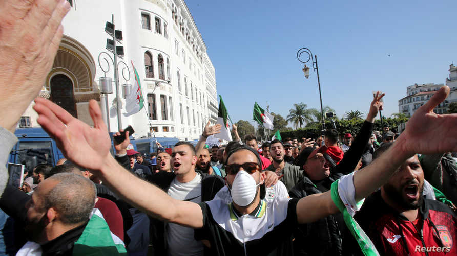 FILE PHOTO: A demonstrator wearing a face mask gestures during an anti-government protest in Algiers, Algeria February 28, 2020…
