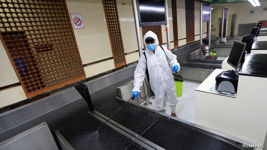 A worker wearing a protective suit sprays interiors departure hall of Baghdad International Airport after Iraq has suspended…