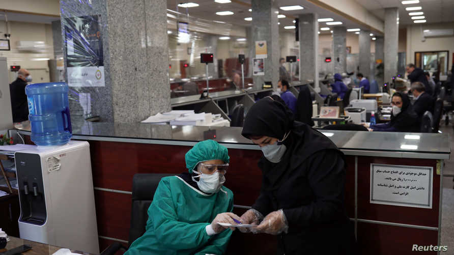 Bank employees wear protective face masks and clothes, following the outbreak of coronavirus, during the work in Tehran, Iran…