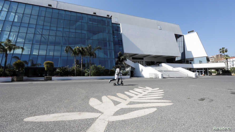 A man skates past a Palme d'Or symbol on the pavement near the Festival palace on the Croisette in Cannes where the Cannes Film…