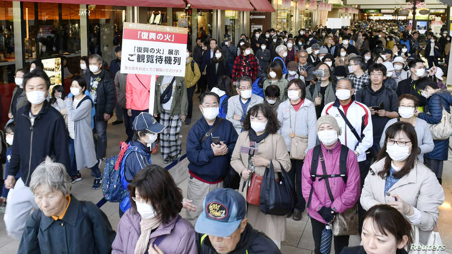 People wearing protective face masks following an outbreak of the coronavirus disease (COVID-19), queue as they try to watch…
