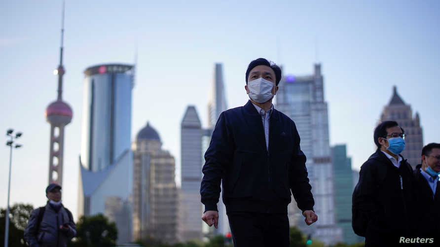 FILE PHOTO: People wear protective face masks, following an outbreak of the novel coronavirus disease (COVID-19), at Lujiazui…