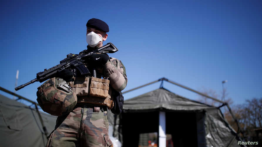 A French soldier, wearing a protective face mask, stands next to tents at a miitary field hospital near Mulhouse hospital as…