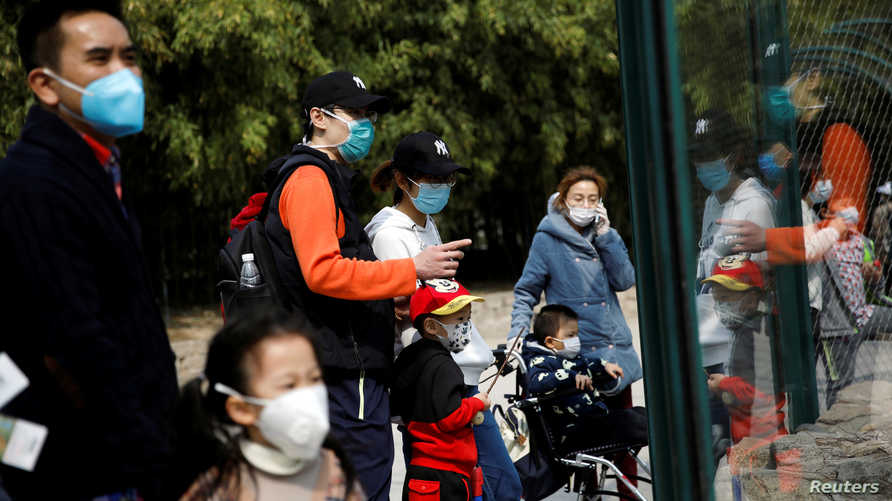 People wearing face masks visit Beijing Zoo, which has partially reopened after closing in late January due to the coronavirus…