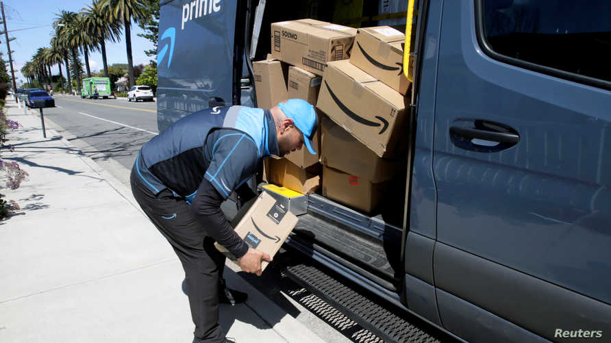 Joseph Alvarado picks up a package while making deliveries for Amazon during the outbreak of the coronavirus disease (COVID-19)…