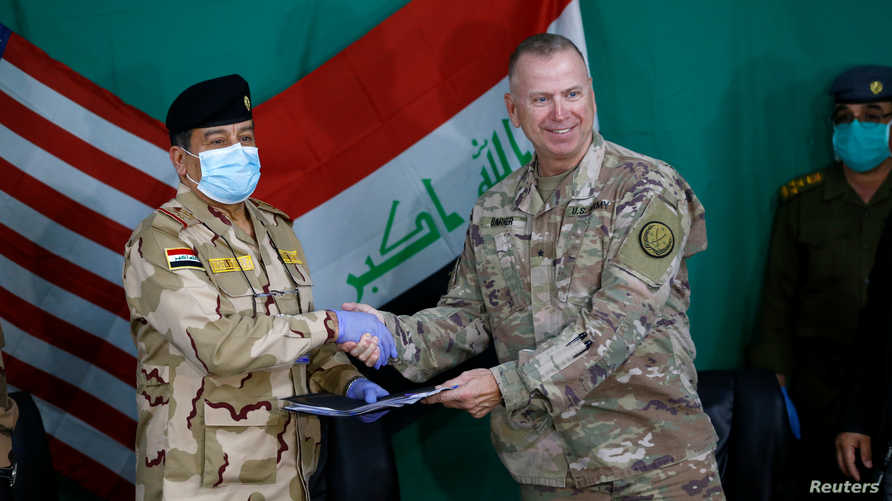 U.S. Brigadier General Vincent Barker shakes hands with Iraqi General Mohammed Fadel during the hand over of US-led coalition…
