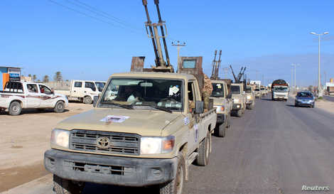 FILE PHOTO: Military vehicles of the Libyan internationally recognised government forces head out to the front line from…