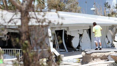 رجل ينظر إلى منزل دمره الإعصار