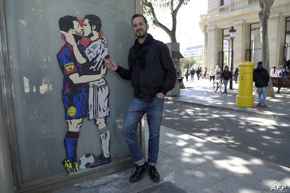 أحد المارة يقف بجانب رسم غرافيتي لقبلة ميسي ورونالدو في برشلونة