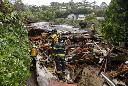 عناصر في جهاز الإطفاء يتفقدون منزلا دمره انزلاق طيني في سوساليتو بكاليفورنيا