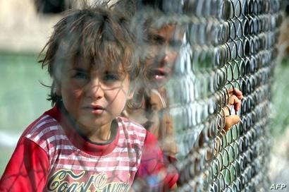 طفل عراقي ينظر من خلف السياج في مخيم الخازر للاجئين
