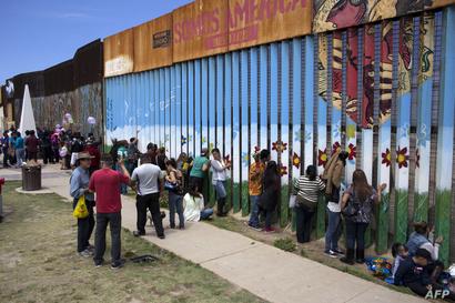 مكسيكيون أمام السياج على الحدود مع أميركا