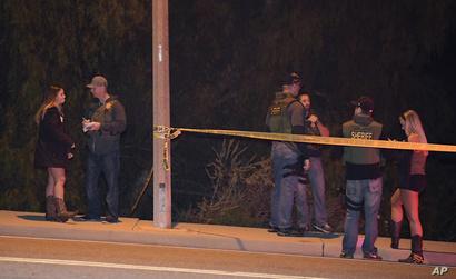 عناصر في الشرطة يتحدثون إلى شهود عيان خارج الحانة التي شهدت إطلاق النار