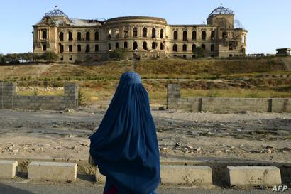 امرأة أفغانية تقف أمام قصر دارول أمان، مسكن الملك الأفغاني السابق أمان الله خان، في كابل