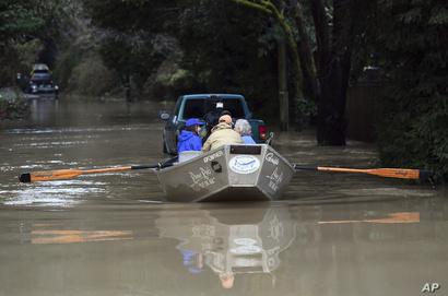 أحد سكان غيرنفيل في كاليفورنيا يستخدم قاربا للتنقل في إحدى المناطق التي اجتحاتها فيضانات