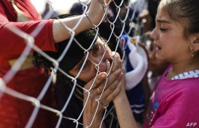 سيدة عراقية تقبل يد طفلة من عائلتها بعد رؤيتها لأول مرة منذ سنتين