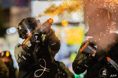 أحد العناصر في شرطة هونغ كونغ يطلق الغاز المسيل للدموع لتفريق المتظاهرين في 2 نوفمبر 2019