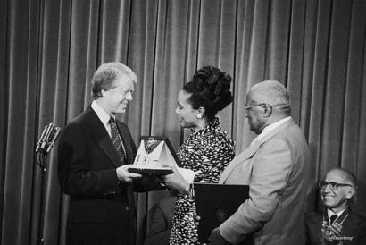 الرئيس الأسبق جيمي كارتر يمنح الميدالية الرئاسية للحرية إلى مارتن لوثر كنغ في 1977 حيث تظهر زوجته وهي تتسلم الميدالية-الصورة مأخوذة من موقع الميدالية الرئاسية للحرية