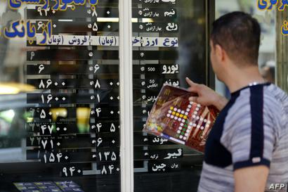 إيراني يراقب أسعار صرف العملات أمام بنك في طهران- أرشيف
