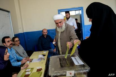 تركيان يدليان بصوتيهما في أحد مراكز الاقتراع في إسطنبول
