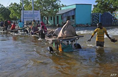 مدنيون شمالي مقديشو ينزحون بسبب الفيضانات على ظهور الحمير في 26 أيار/مايو