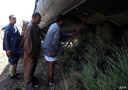 مواطنون يتفقدون عربات القطار التي تعرضت للحادث
