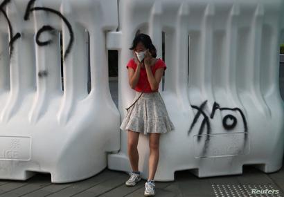 فتاة تحاول حماية نفسها من الغاز المسيل للدموع في احتجاجات اندلعت الأحد أمام مقر الحكومة في هونغ كونغ