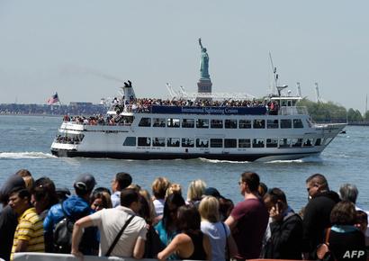 مركب سياح قرب تمثال الحرية في نيويورك