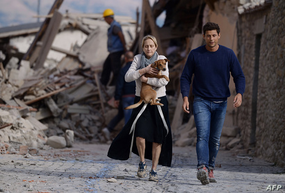 سيدة تحمل كلبها بعد نجاتهما من الزلزال