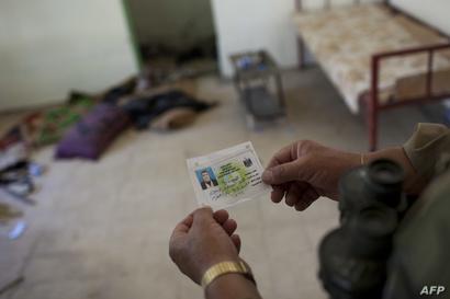 جندي من البيشمركة ينظر إلى بطاقة شخصية تركها أحد النازحين من المدينة