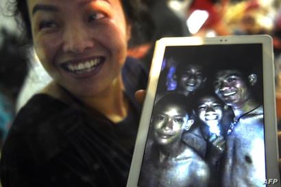 امرأة تعرض صورة لأربعة من الصبية الناجين