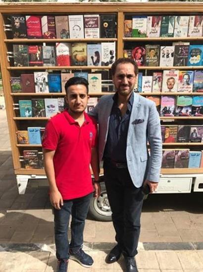 علي الموسوي مع الفنان العراقي نصير شمة بجانب المكتبة الجوالة