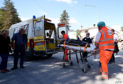 رجال الإنقاذ يحملون جثة أحد الضحايا