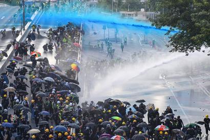 يستخدم المحتجون المظلات في مواجهة مدافع المياه