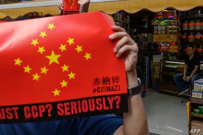 محتج يحمل علم الصين والنجوم التي عليه تشكل شعار النازية في احتجاجات هونغ كونغ
