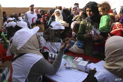 نازحون في مخيم الركبان خلال حصولهم على المساعدات والعلاج الطبي