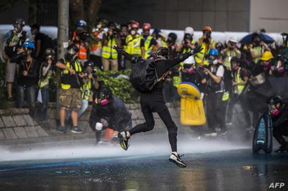 محتجون يتسلحون بأقنعة الغاز بعد إطلاق الشرطة الغاز المسيل للدموع عليهم