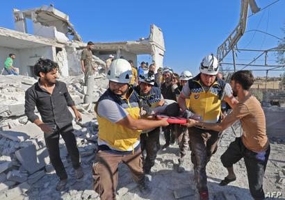 عناصر في الدفاع المدني يحملون أحد ضحايا القصف في إدلب