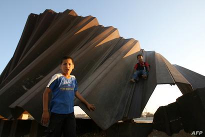 أطفال فلسيطينيون يلعبون على ما يفترض أنه كان جدارا عازلا بين غزة ومصر . أرشيفية