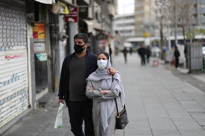 إيرانيان يضعان كمامتين في أحد شوارع طهران. ووسط الانتشار الواسع لكوفيد-19 في إيران لا تقدم السلطات أرقاما دقيقة عن الإصابات والوفيات