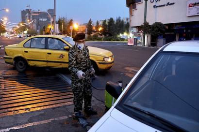 أحد عناصر الحرس الثوري يعقم سيارة في طهران