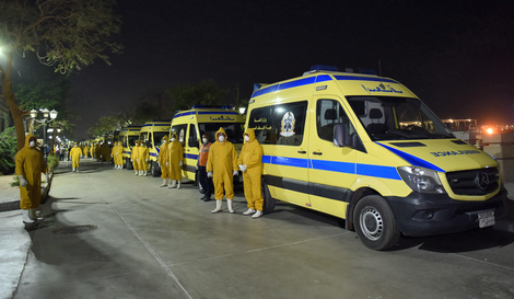 Egyptian health ministry emergency responders stand next to ambulances ready on the scene to transport suspected COVID-19…