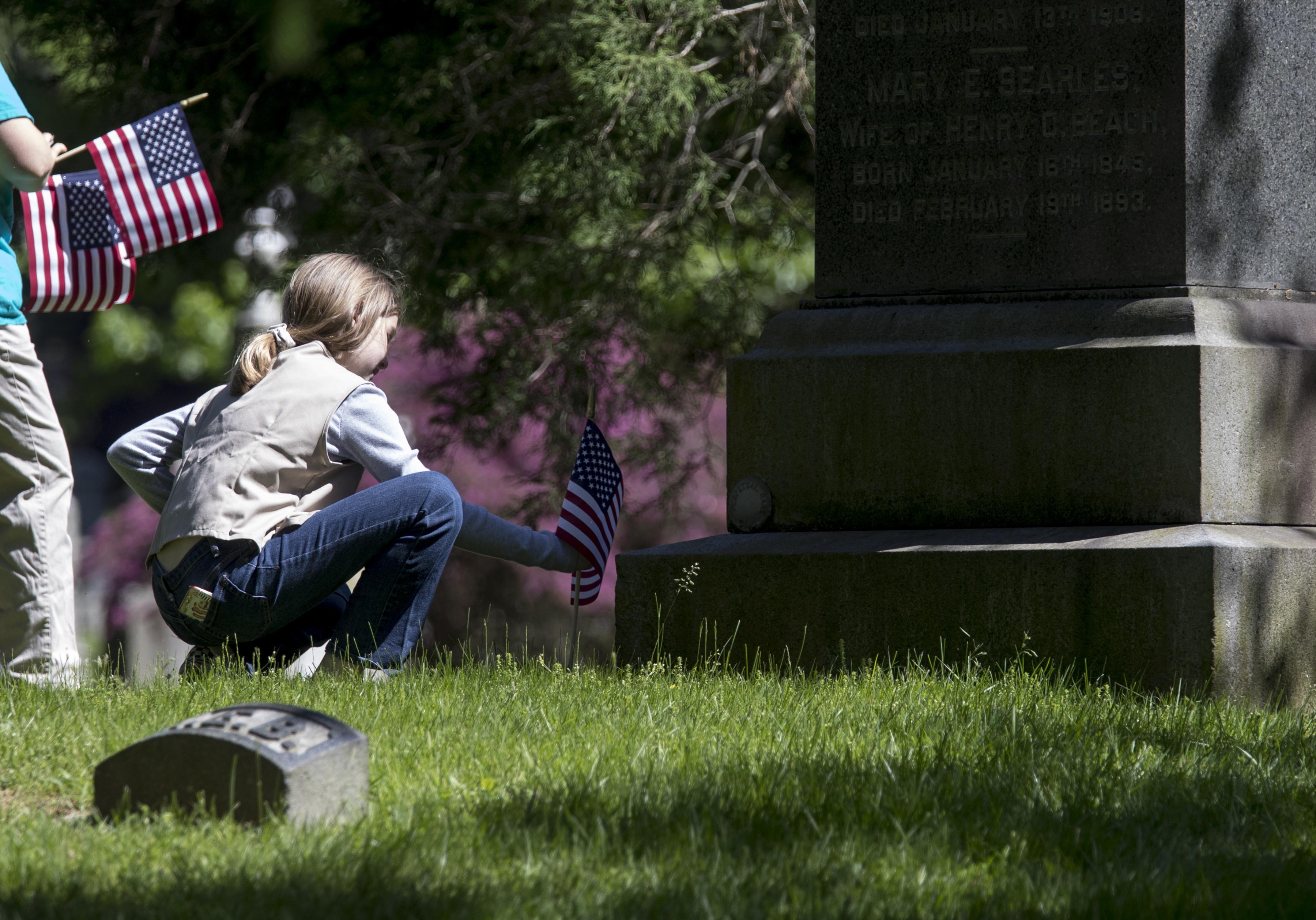 فتاة تضع الزهور على مقبرة عسكري أميركي في نيويورك قضى في الحرب العالمية الثانية