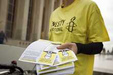 An amnesty International activist distributes leaflets during a protest against the visit in France of Russian President…
